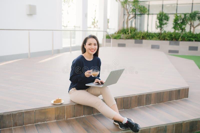 Mujer joven que usa el ordenador portátil Muchacha hermosa que trabaja en revestimiento imagen de archivo libre de regalías