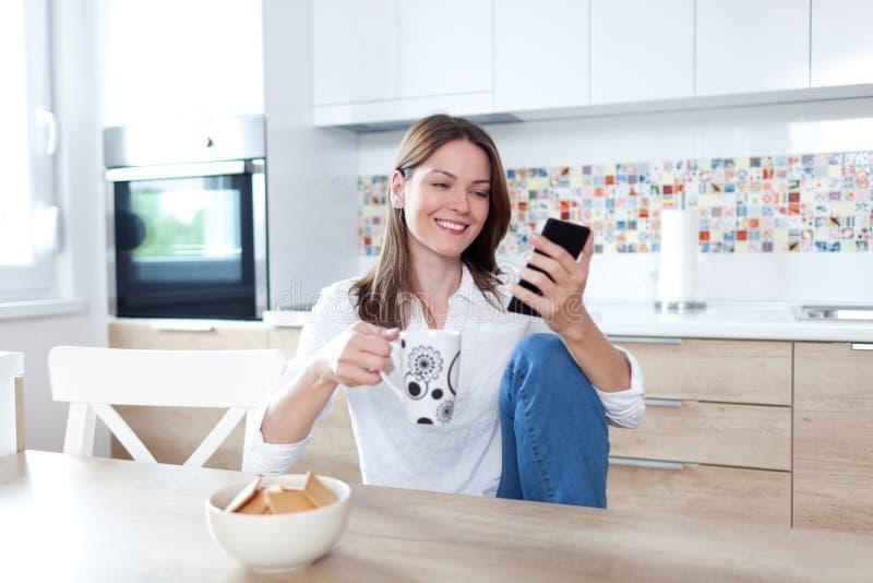 Mujer joven que usa el teléfono celular en la cocina imágenes de archivo libres de regalías