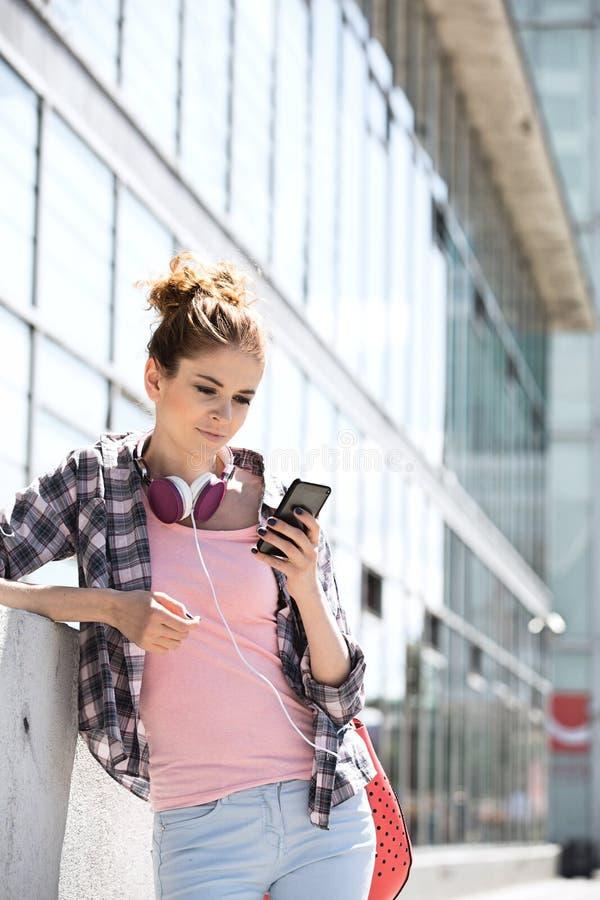Mujer joven que usa el teléfono elegante fuera del edificio de oficinas foto de archivo libre de regalías