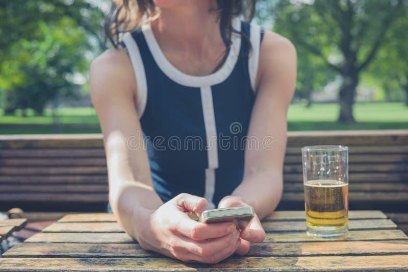 Mujer joven que usa el teléfono elegante y bebiendo la cerveza imágenes de archivo libres de regalías