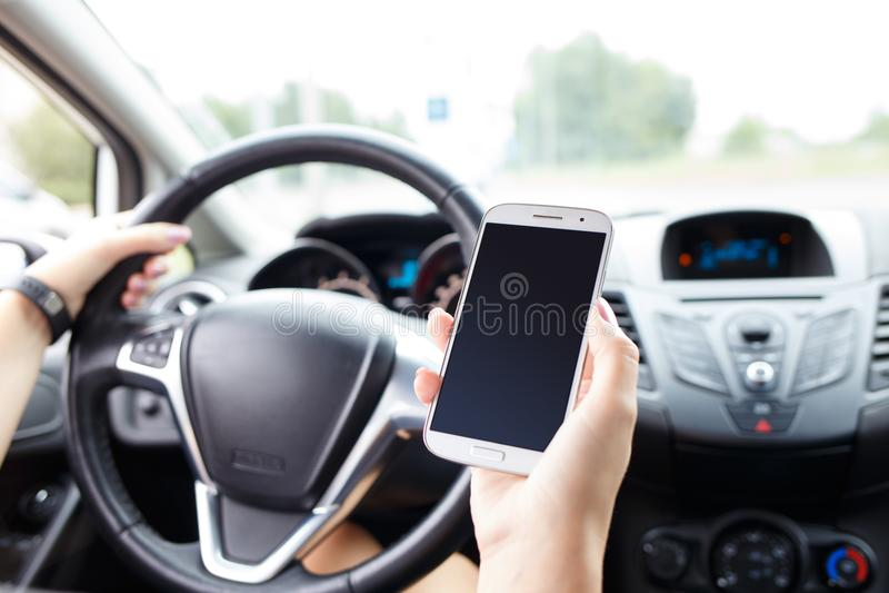 Mujer joven que usa el teléfono móvil en un coche en el camino imágenes de archivo libres de regalías