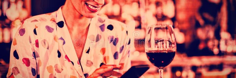 Mujer joven que usa el teléfono móvil mientras que comiendo vino imagen de archivo
