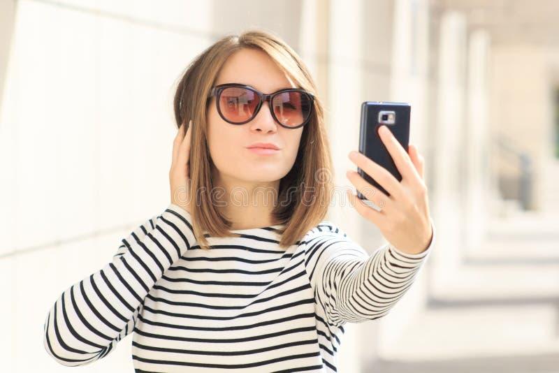 Mujer joven que usa el teléfono móvil que toma la imagen del selfie, autorretrato imagen de archivo libre de regalías