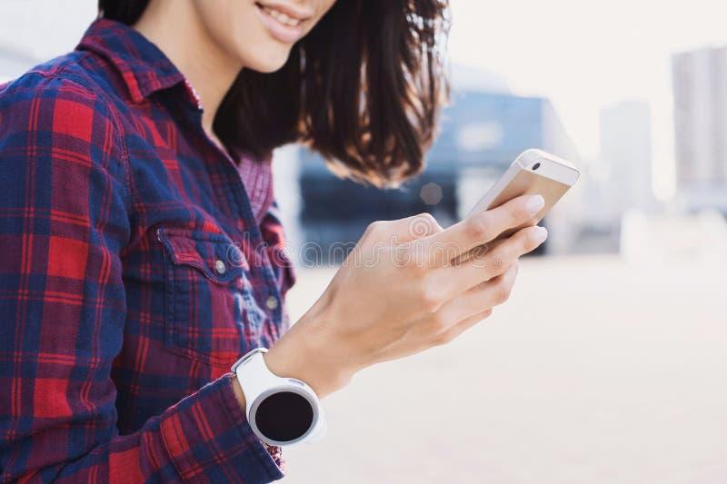 Mujer joven que usa el tel?fono elegante al aire libre fotos de archivo libres de regalías