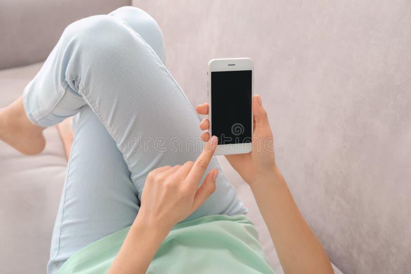 Mujer joven que usa el tel?fono en casa fotos de archivo