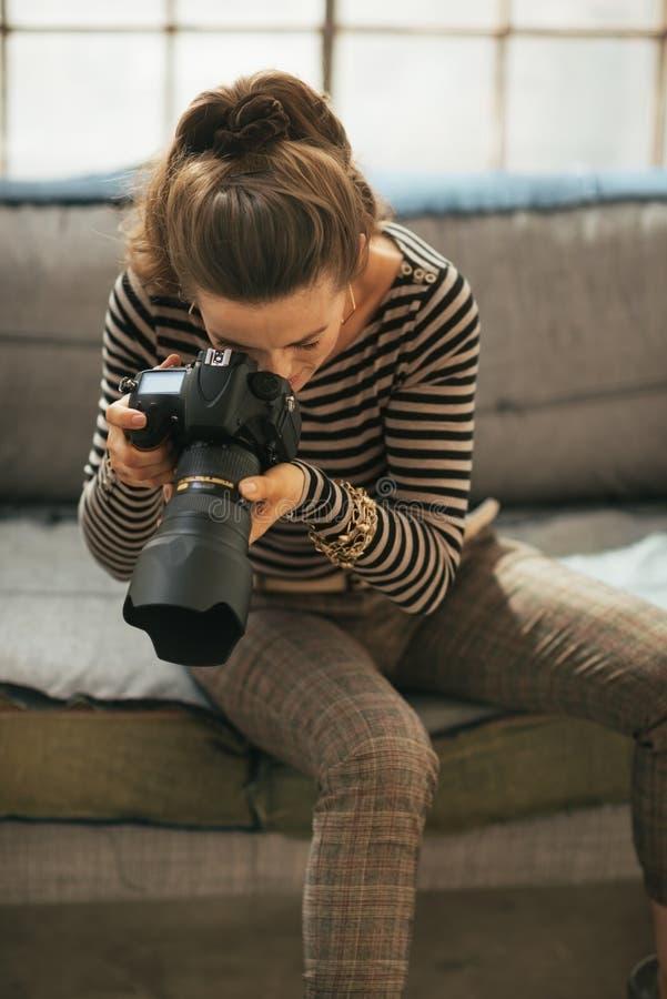 Mujer joven que usa la cámara moderna de la foto del dslr imagen de archivo libre de regalías