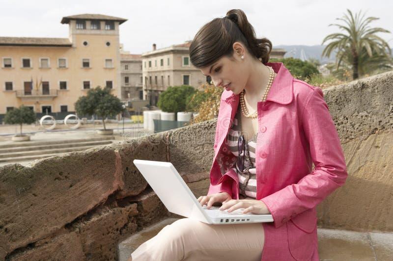 Mujer joven que usa la computadora portátil en parque fotografía de archivo