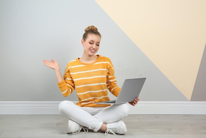 Mujer joven que usa la computadora port?til en suelo imagen de archivo libre de regalías