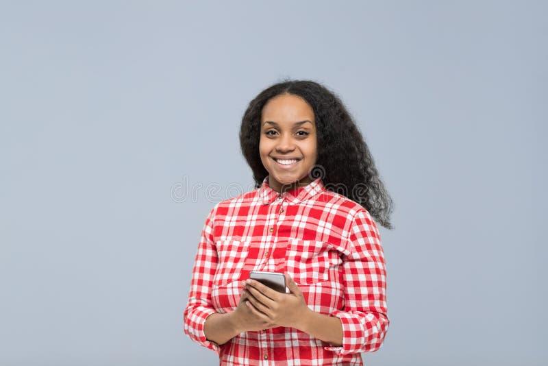 Mujer joven que usa la sonrisa feliz de la muchacha afroamericana elegante del teléfono de la célula que charla en línea fotos de archivo libres de regalías