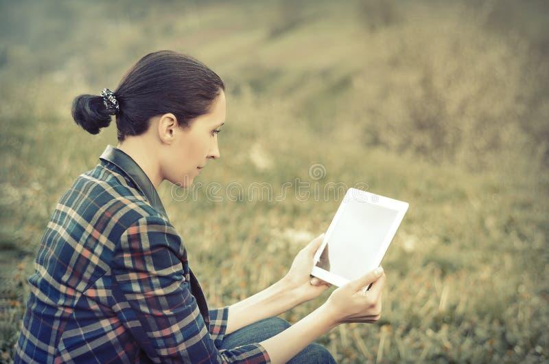 Mujer joven que usa la tableta al aire libre foto de archivo
