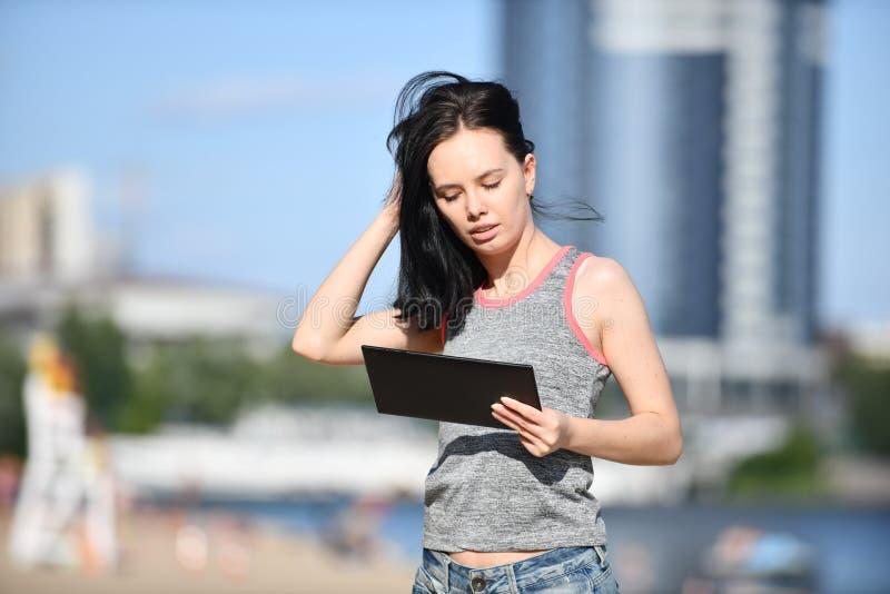 Mujer joven que usa la tableta digital en el parque fotografía de archivo