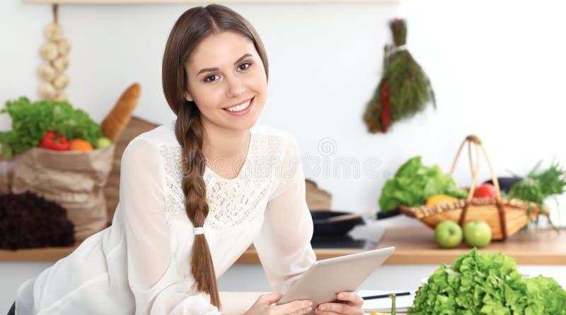 Mujer joven que usa la tableta mientras que cocina o hace compras en línea en cocina Muchacha que mira la cámara Sano imagenes de archivo