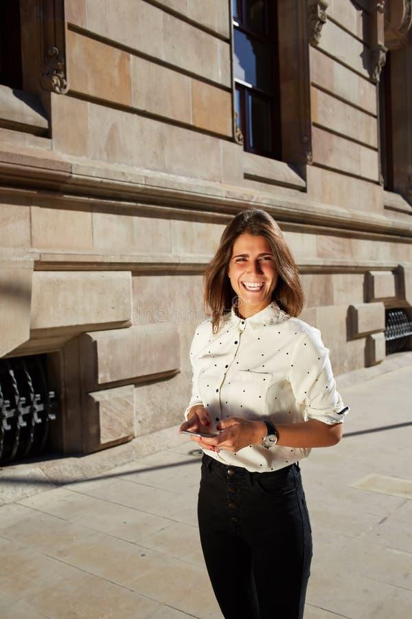 Mujer joven que usa las tecnologías modernas para charlar con sus amigos, mensaje que manda un SMS de la muchacha feliz del incon imágenes de archivo libres de regalías
