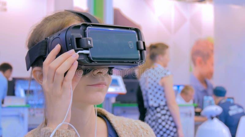 Mujer joven que usa los vidrios de la realidad virtual imagenes de archivo