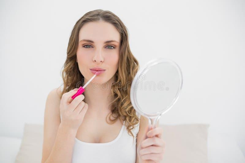 Mujer joven que usa lustre del labio y mirando en la cámara imágenes de archivo libres de regalías