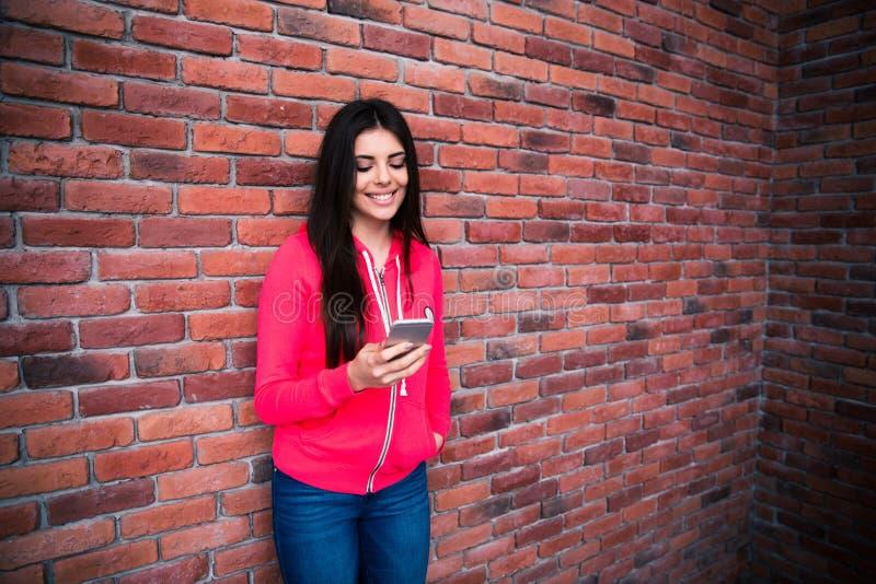 Mujer joven que usa smartphone sobre la pared de ladrillo imagenes de archivo
