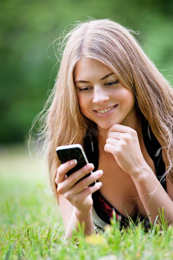 Mujer joven que usa su pda fotos de archivo libres de regalías