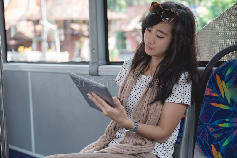 Mujer joven que usa su tableta digital en el autobús fotos de archivo libres de regalías