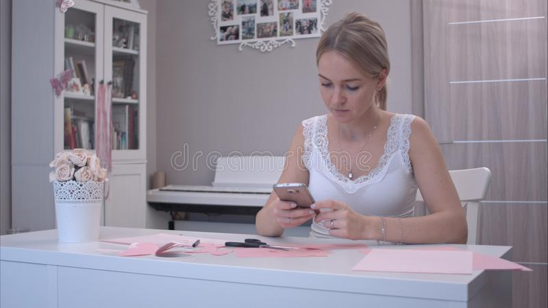 Mujer joven que usa su teléfono mientras que corta las mariposas de papel foto de archivo libre de regalías