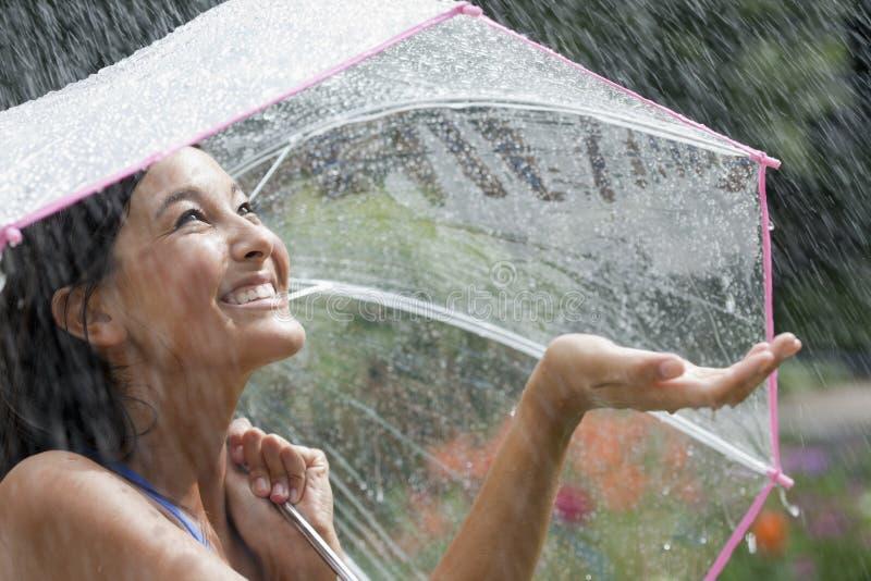 Mujer joven que usa un paraguas en lluvia imagenes de archivo