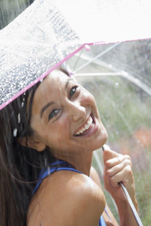 Mujer joven que usa un paraguas en lluvia fotografía de archivo
