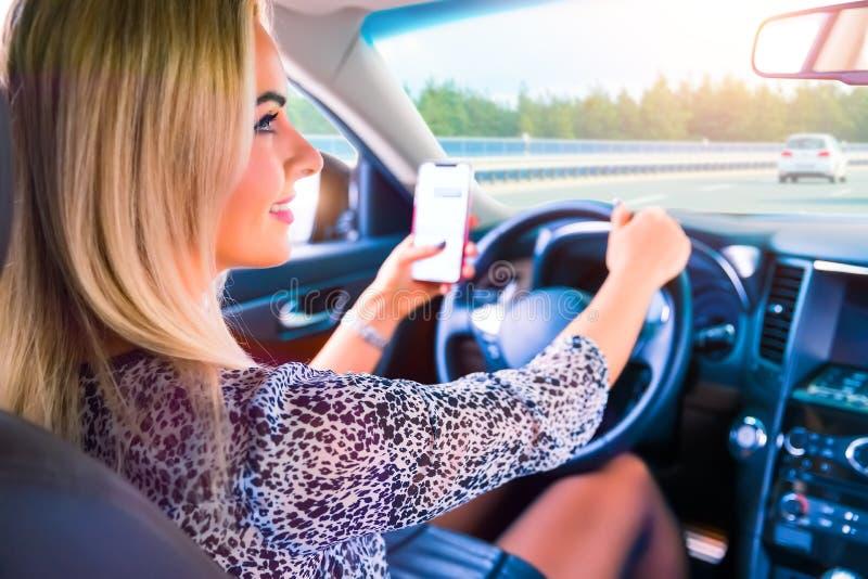 Mujer joven que usa un smartphone mientras que conduce un coche fotos de archivo libres de regalías