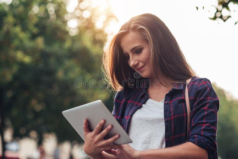 Mujer joven que usa una tableta mientras que hacia fuera en la ciudad fotos de archivo libres de regalías