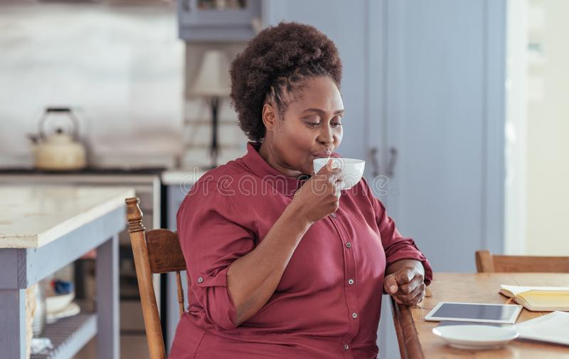 Mujer joven que usa una tableta y bebiendo el café en casa imagenes de archivo