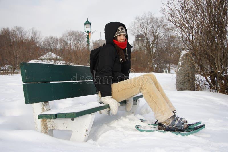 Mujer joven que va de excursión con los zapatos/las raquetas de la nieve imagen de archivo libre de regalías