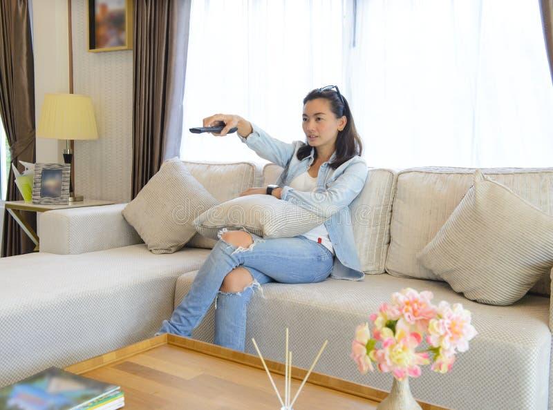 Mujer joven que ve la TV mientras que se sienta en un sofá fotografía de archivo