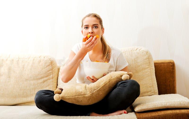 Mujer joven que ve la TV y que come microprocesadores imágenes de archivo libres de regalías