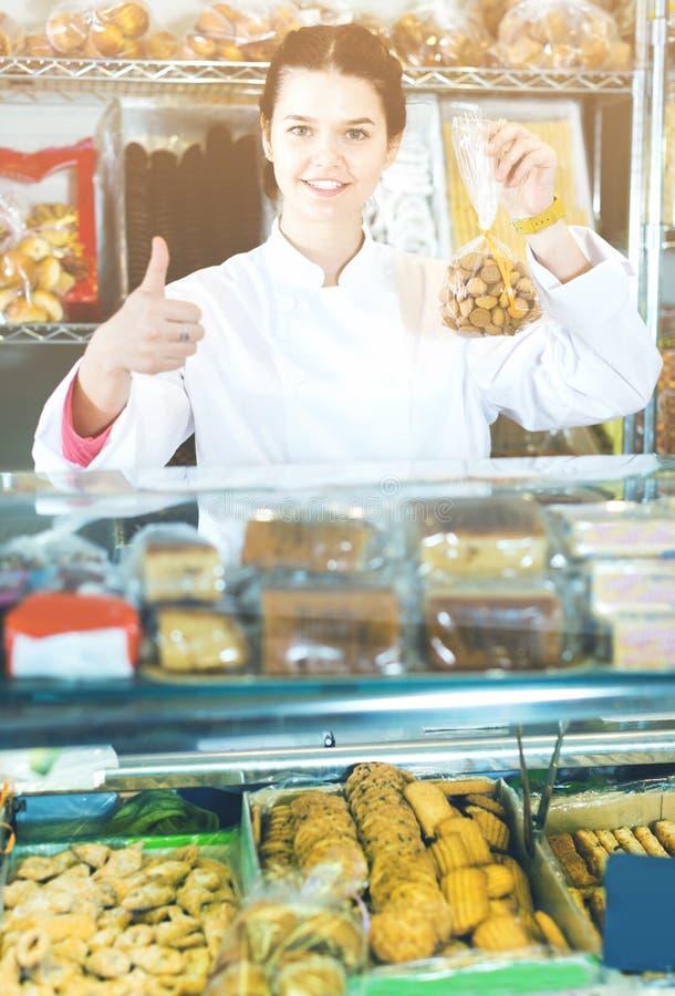 Mujer joven que vende las galletas y otros rellenos fotografía de archivo libre de regalías
