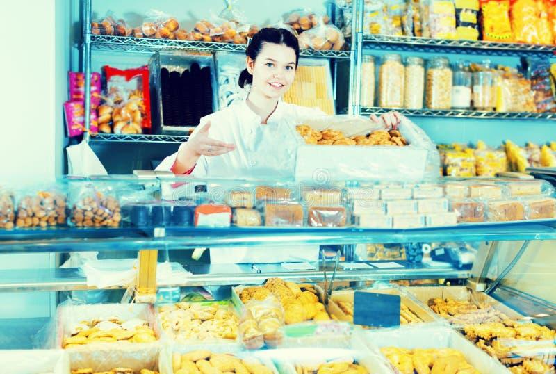 Mujer joven que vende las galletas y otros rellenos fotos de archivo libres de regalías