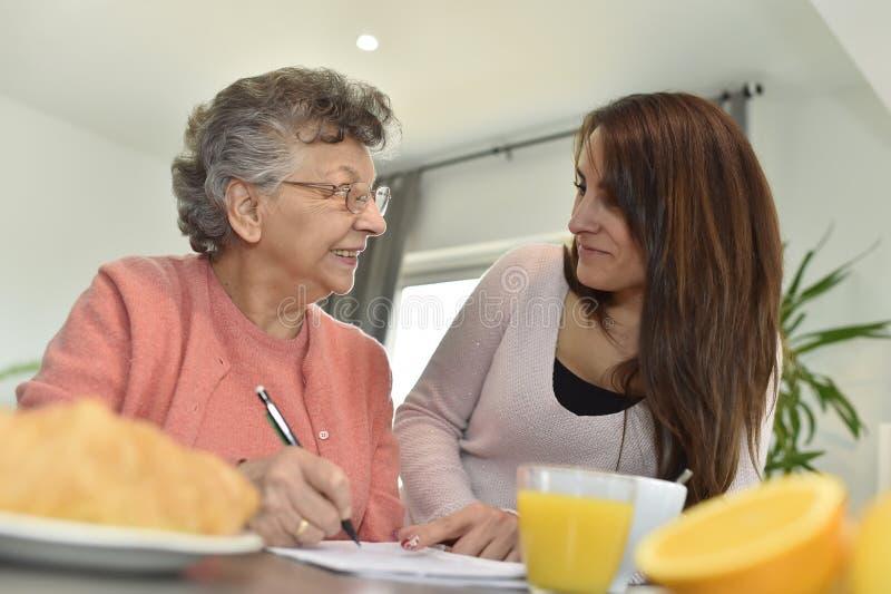 Mujer joven que visita a una mujer mayor en una casa de retiro imagen de archivo
