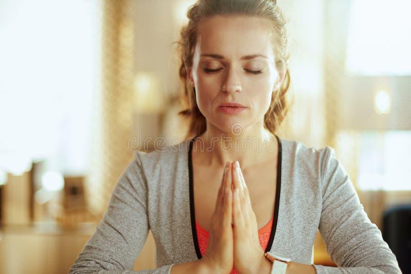 Mujer joven relajada de los deportes en meditar moderno de la sala de estar fotografía de archivo libre de regalías