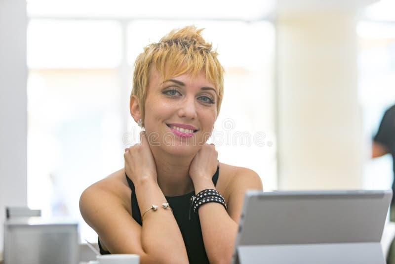 Mujer joven relajada elegante con una sonrisa amistosa imagen de archivo
