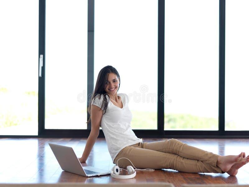 Mujer joven relajada en casa que trabaja en el ordenador portátil imagenes de archivo