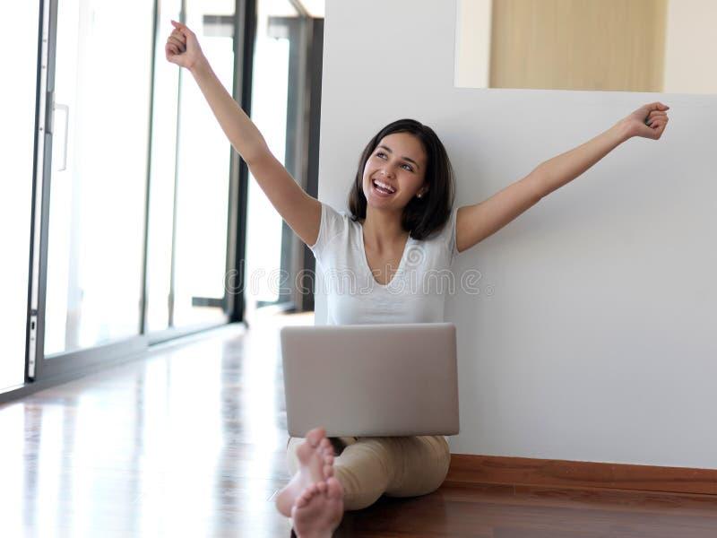 Mujer joven relajada en casa que trabaja en el ordenador portátil imágenes de archivo libres de regalías