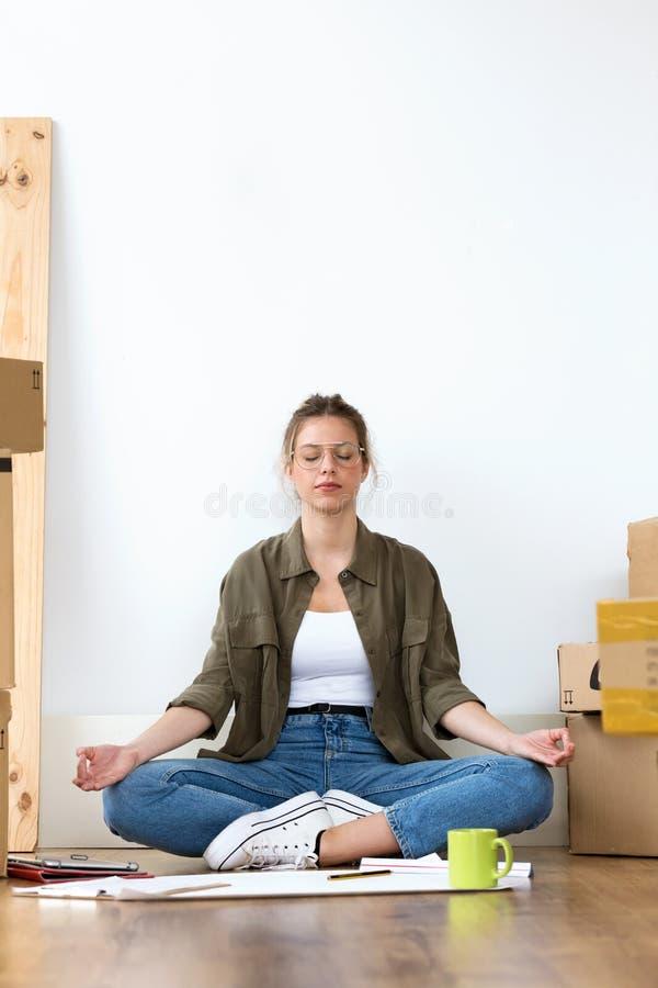 Mujer joven relajada que hace yoga mientras que se sienta en el piso de su nueva casa imagenes de archivo
