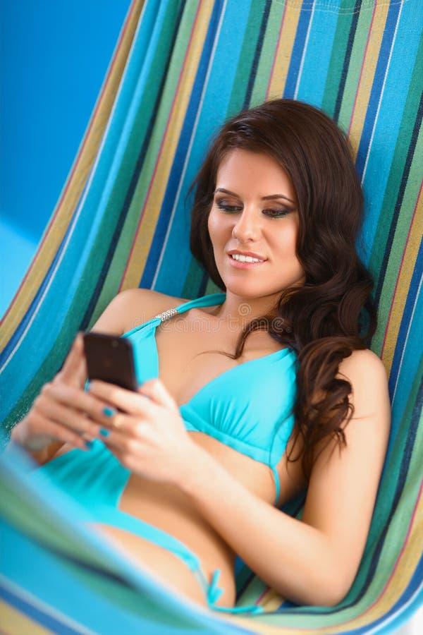 Mujer joven relajada que mira el teléfono móvil adentro fotos de archivo