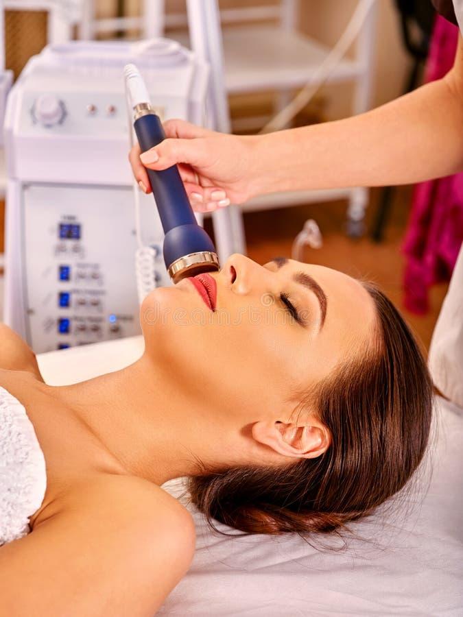 Mujer joven relajada que recibe masaje facial eléctrico fotos de archivo