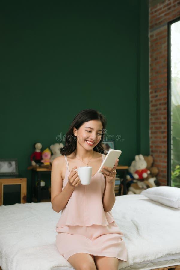 Mujer joven relajada que se sienta en cama con una taza de café y de teléfono móvil foto de archivo libre de regalías
