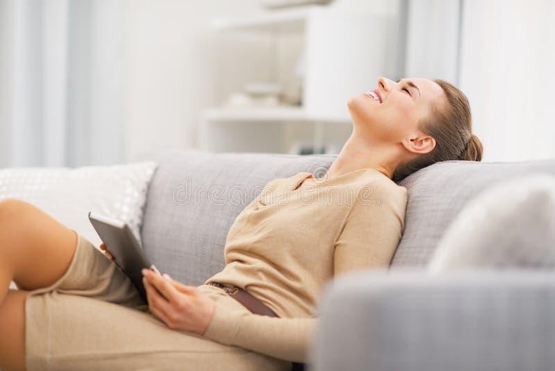 Mujer joven relajada que se sienta en el sofá con PC de la tableta imágenes de archivo libres de regalías