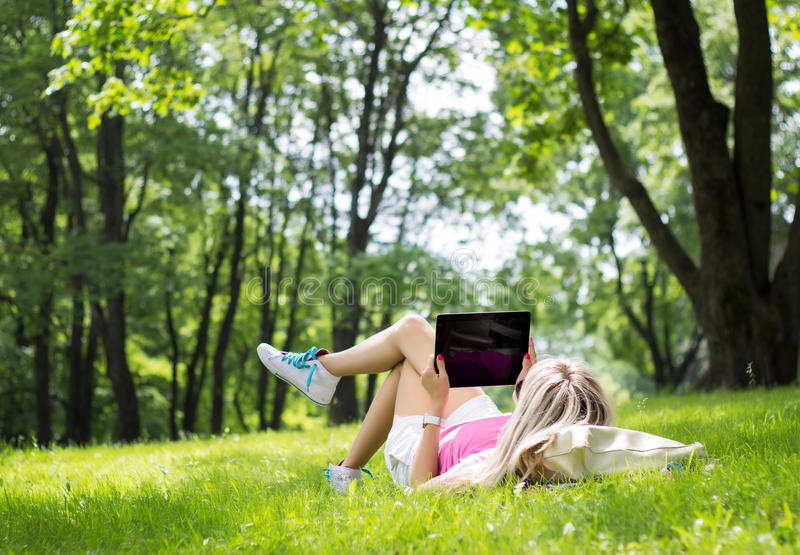 Mujer joven relajada que usa la tableta al aire libre foto de archivo libre de regalías