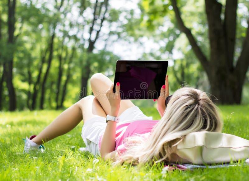 Mujer joven relajada que usa la tableta al aire libre fotos de archivo libres de regalías