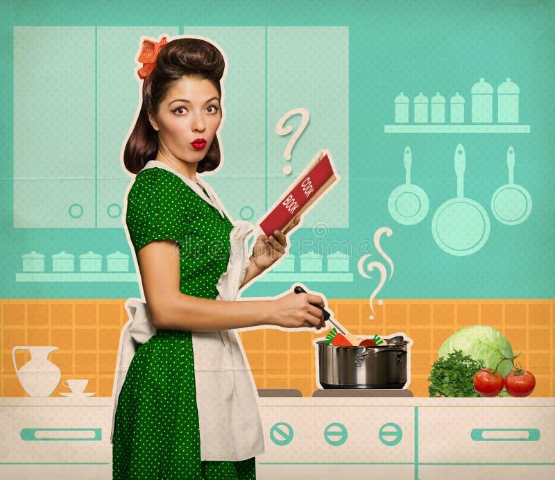 Mujer joven retra que cocina y que lee el libro de la receta en su cocina imagenes de archivo