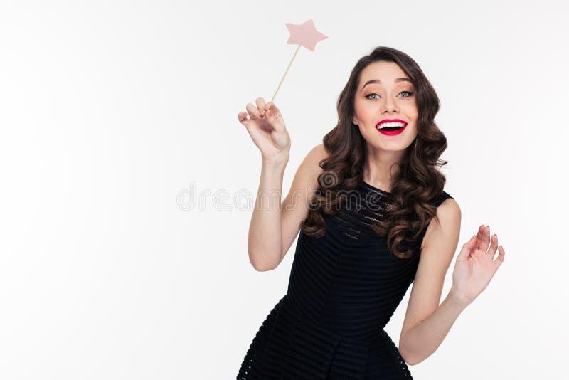 Mujer joven rizada hermosa alegre que presenta con la vara mágica fotografía de archivo