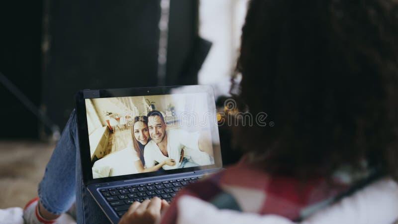 Mujer joven rizada que tiene charla video con los amigos que usan la cámara del ordenador portátil mientras que miente en cama imagenes de archivo