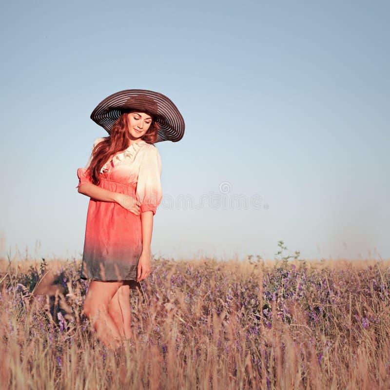 Mujer joven romántica en el sombrero que se coloca en prado en día de verano caliente fotos de archivo libres de regalías
