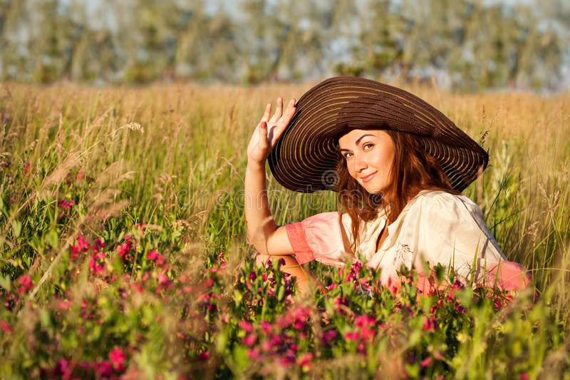 Mujer joven romántica en el sombrero que se coloca en prado en día de verano caliente foto de archivo libre de regalías